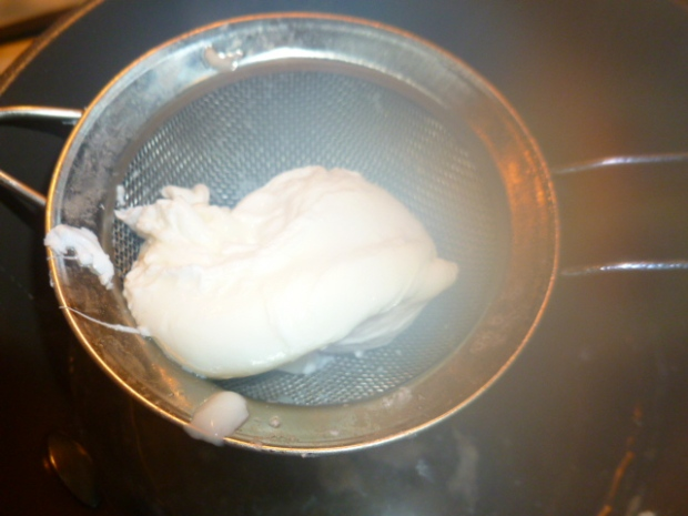 Lift the poached egg gently, with a slotted spoon or a small sieve. Place on a paper towel to absorb access water. Repeat with the second egg.